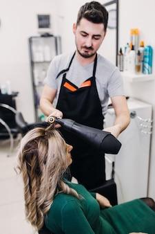 Bella acconciatura di donna matura dopo aver tinto i capelli e aver messo in evidenza nel parrucchiere.