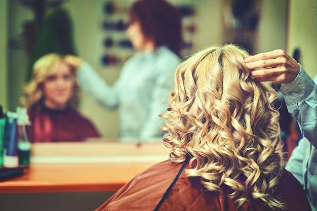 Bella acconciatura di giovane donna dopo aver tinto i capelli e aver messo in evidenza nel parrucchiere.