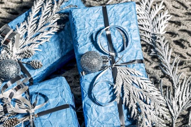 Bellissimi regali di capodanno fatti a mano in colore blu argento. cartolina di natale con sfondo argento e blu. decorazione natalizia con pino, abete e scatole regalo. avvicinamento,