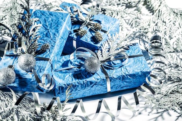 Bellissimi regali di capodanno fatti a mano in colore blu argento. cartolina di natale con sfondo argento e blu. decorazione natalizia con pino, abete e scatole regalo. avvicinamento.