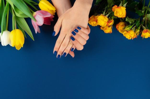 Belle mani con manicure con rose gialle e tulipani colorati