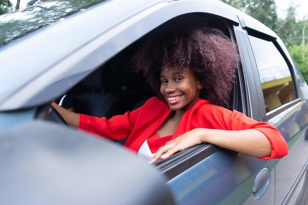 Bella e felice donna afro-americana alla guida di un'auto