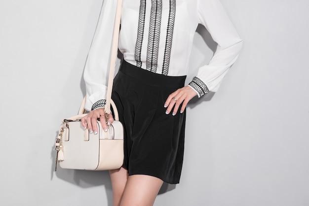 Bella donna asiatica felice che tiene una borsa in piedi su uno sfondo grigio.