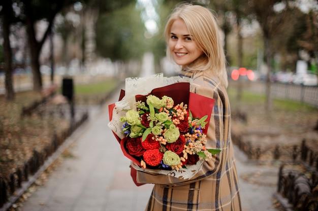 Bella donna bionda felice in cappotto a quadri in possesso di un brillante mazzo di fiori che camminano sul vicolo