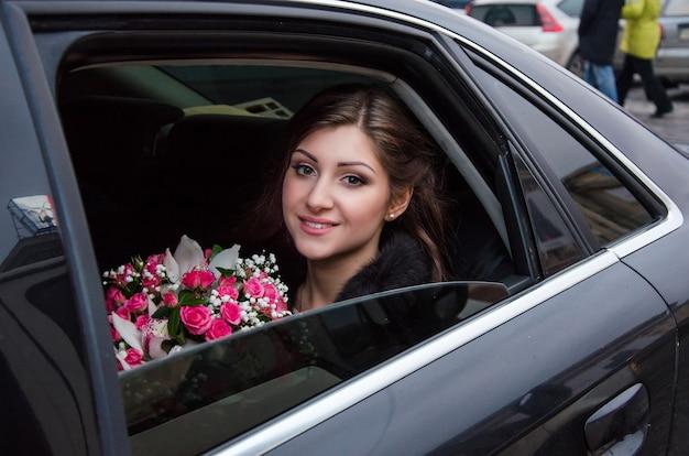 Bella sposa felice in macchina il giorno del matrimonio