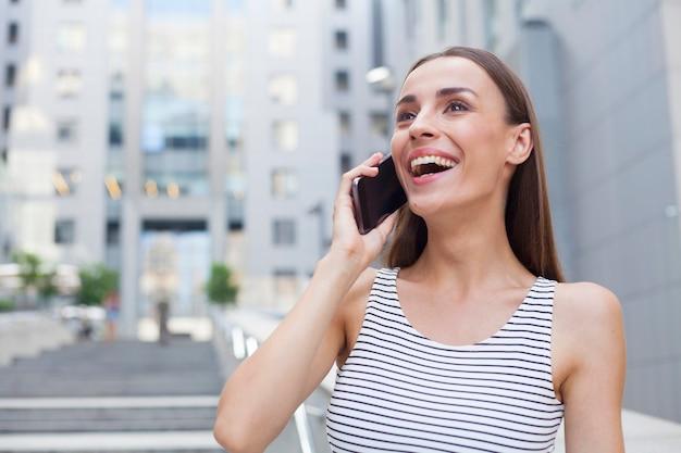 Bella donna bruna felice sta parlando sul suo smartphone e distoglie lo sguardo.