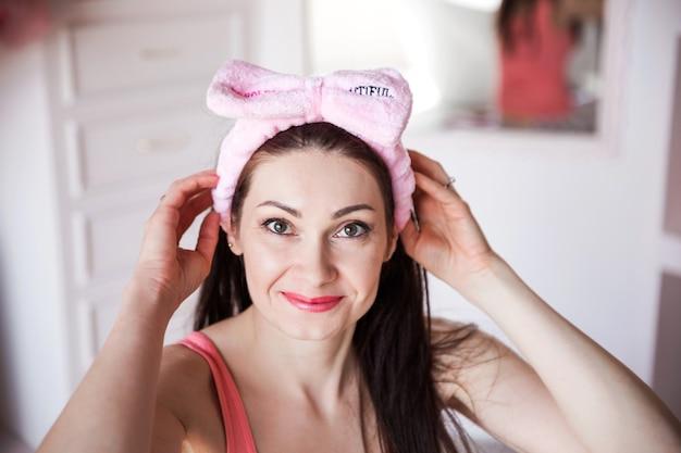 Bella e felice donna castana in benda cosmetica rosa e pigiama in posa per la fotocamera nella sua camera da letto.
