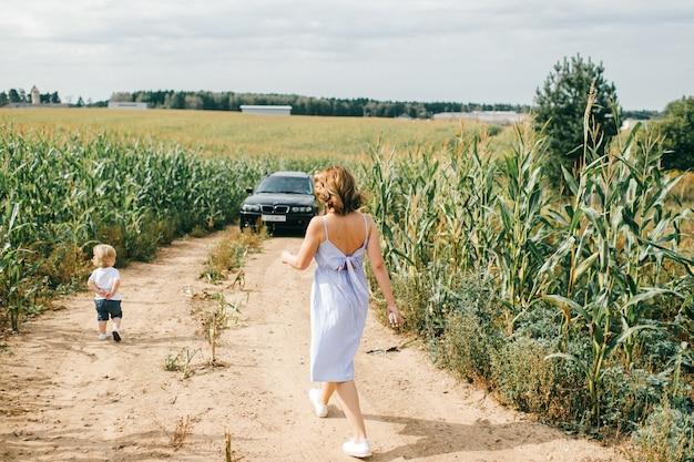 La bella mamma caucasica felice cammina con il suo ragazzino biondo vicino al campo di grano.
