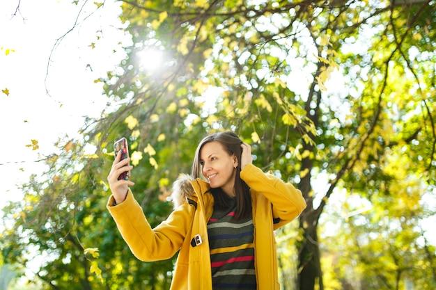 La bella donna dai capelli castani allegra felice in un cappotto giallo e maniche lunghe a righe che fa selfie sul cellulare nel parco cittadino autunnale in una giornata calda. foglie d'oro autunnali.