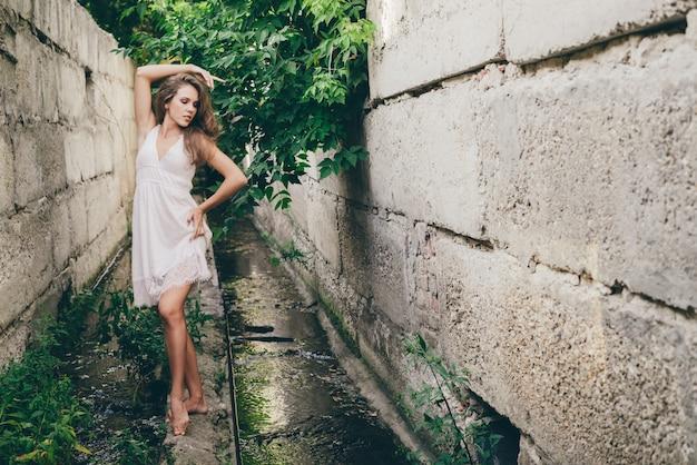 Bella ragazza di dancing felice con capelli naturali ricci in vestito bianco vicino alle foglie verdi dell'albero. ritratto di bellezza estiva. la donna dei sogni ama la natura. donna ispirata con vista da sogno nel lungo tunnel nella foresta