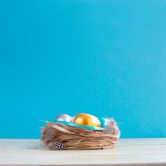 Bella bandiera di saluto di festa di pasqua felice con nido di pasqua con uova colorate e decorato con nastri su fondo in legno chiaro con spazio copia per testo su blu