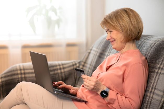 Bella donna senior anziana felice che si siede allo strato a casa con il computer portatile, acquisto in linea con carta di credito