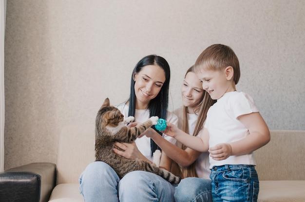 Bella mamma di famiglia felice e due bambini che giocano con un gatto seduto sul divano.