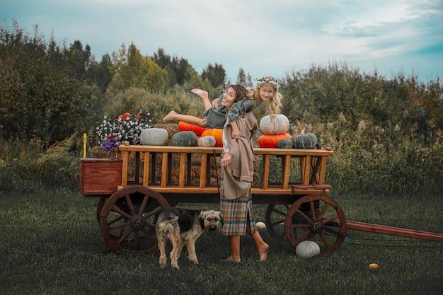 Bella madre di famiglia felice figlia e cane da compagnia insieme su un carretto di legno con zucche