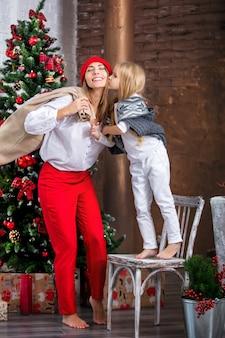 Bella famiglia felice madre e figlia insieme in un giorno festivo all'albero di natale