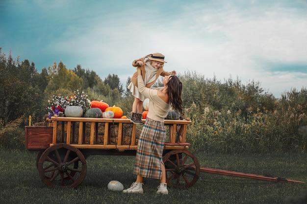 Bella famiglia felice madre e figlia insieme su un carretto di legno con zucche colorate