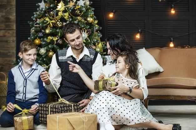 Bella madre di famiglia felice padre figlio e figlia per festeggiare il natale insieme a casa