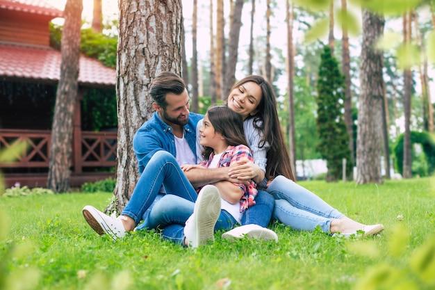Bella famiglia felice seduti insieme sull'erba e si abbracciano