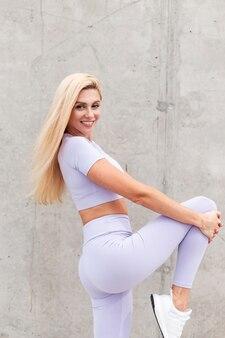 Bella donna modello di fitness felice con un sorriso in abito sportivo viola alla moda che fa stretching sullo sfondo di un muro grigio cemento