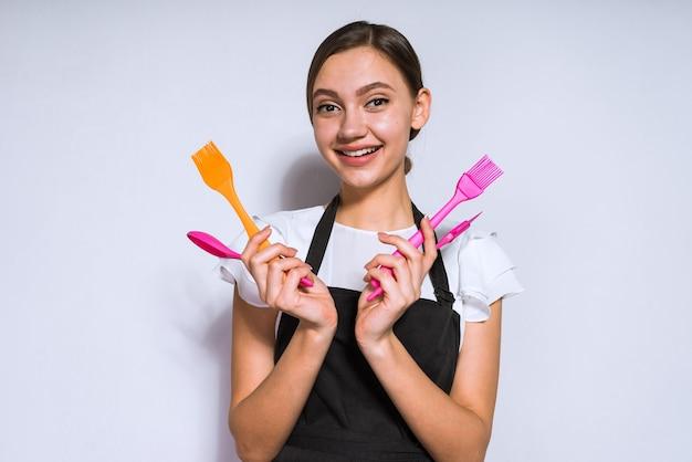 Bella ragazza felice che cucina in grembiule nero con in mano elettrodomestici per cuocere e cucinare, sorridendo