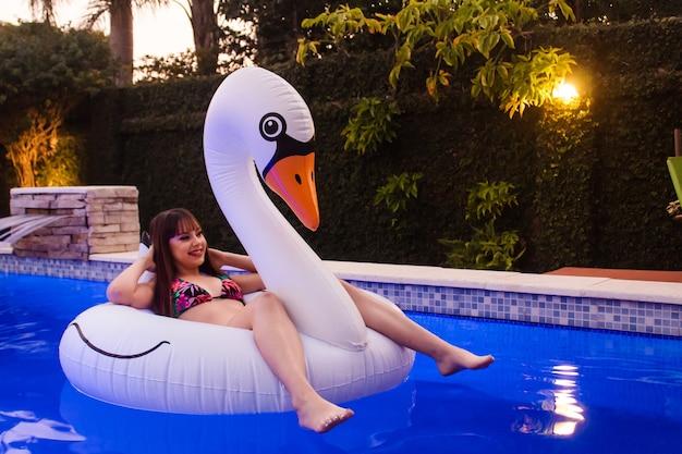 Bella ragazza felice che galleggia su un cigno galleggiante in piscina.