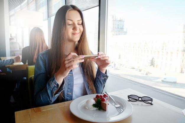 Bella ragazza felice sta facendo foto di cibo nella caffetteria, latte sul tavolo, dessert gelato al cioccolato torta ciliegia menta