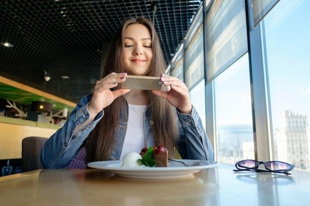 Bella ragazza felice sta facendo foto di cibo in caffè, latte sul tavolo, dessert gelato torta al cioccolato ciliegia menta