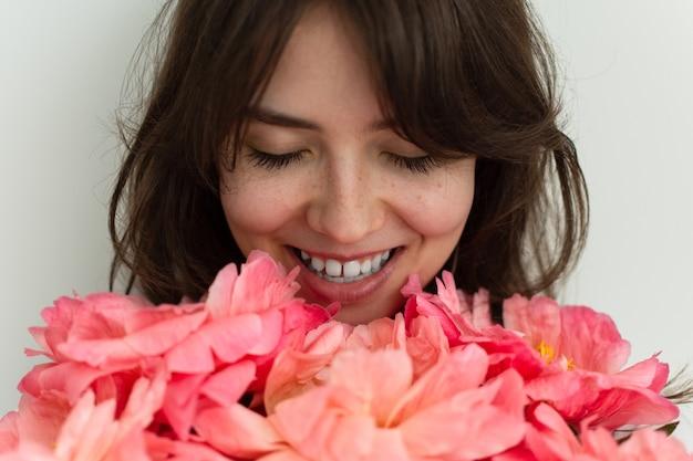 Bella ragazza felice che sorride per il suo compleanno, viso di una ragazza da vicino con peonie, san valentino