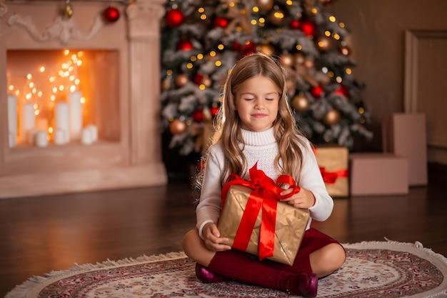 Bella ragazza felice in un maglione bianco con un regalo