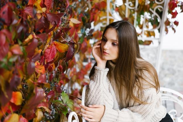 Una bella ragazza felice con i capelli castano chiaro tra le foglie gialle e rosse in un parco in autunno.