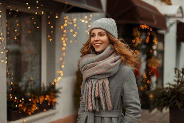 Bella ragazza felice con un sorriso magico in vestiti di maglieria in un cappotto grigio con un cappello lavorato a maglia e una sciarpa che cammina in città sullo sfondo delle luci