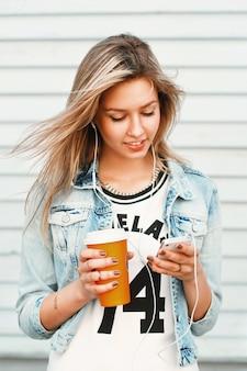 Bella ragazza felice hipster ascolta musica al telefono e beve caffè