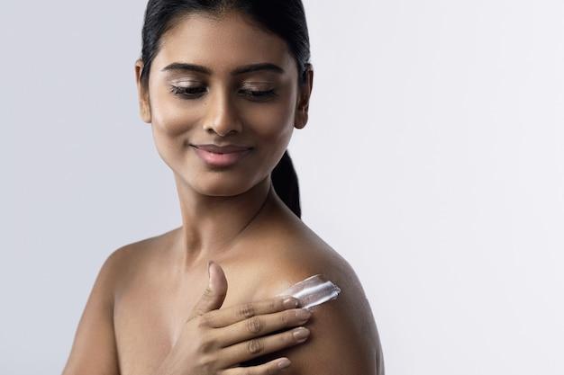 Bella e felice donna indiana che applica crema idratante o crema solare sul suo corpo