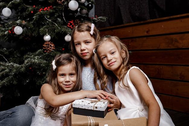 Bei bambini che ridono felici con l'albero di natale