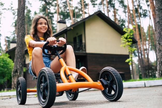 Una bella bambina felice in vacanza sta andando in bicicletta e si diverte nel campo estivo nella foresta
