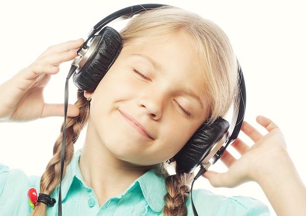 Bella bambina felice con le cuffie. isolato su bianco.