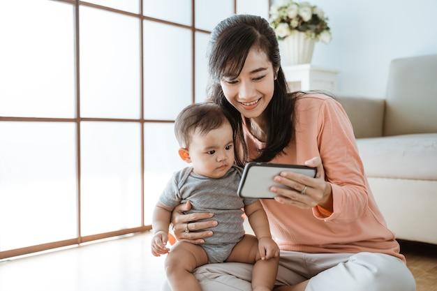 Bella madre felice che gioca con il suo bambino a casa