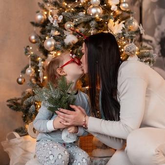 La bella madre felice con la sua piccola figlia fa un bacio sullo sfondo di un albero di natale e luci. vacanze invernali in famiglia a casa