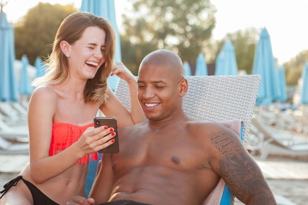 Belle coppie multietniche felici che ridono, facendo uso dello smart phone insieme alla spiaggia, copi lo spazio. amore, viaggi, concetto di vacanza