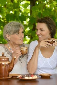Una bella donna anziana felice con sua figlia adulta che beve tè in giardino