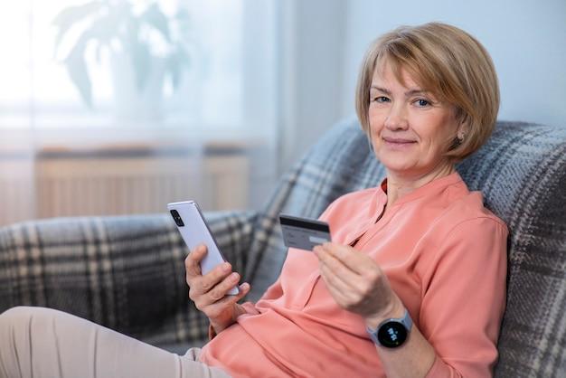 Bella donna senior anziana positiva felice a casa con il telefono cellulare, smartphone, acquisto, utilizzo, tenendo in mano la carta di credito per acquisti in internet, sorridente. concetto di pagamento online.