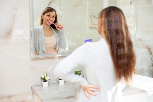 Una bella donna incinta felice in abiti domestici si lava i denti davanti a uno specchio in un bagno luminoso. stile di vita. routine mattutina e serale. igiene. assistenza sanitaria. foto di alta qualità