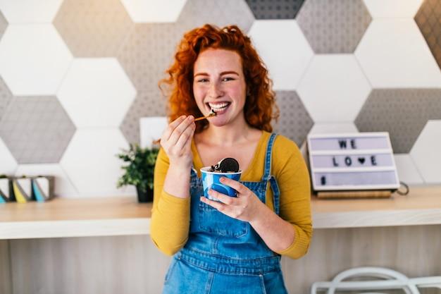Bella e felice donna rossa che si diverte a mangiare un delizioso gelato artigianale.