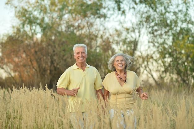 Bella coppia senior felice che corre nel campo estivo