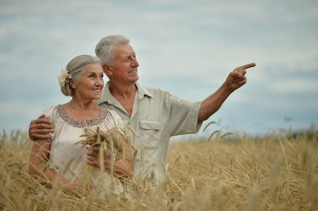 Bella coppia senior felice nel campo estivo, uomo che indica con la mano