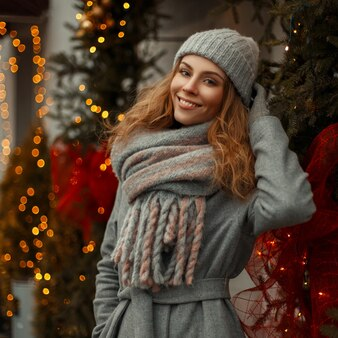 Bella ragazza di smiley felice in vestiti di moda maglieria vintage con un elegante cappello e sciarpa su una vacanza di natale