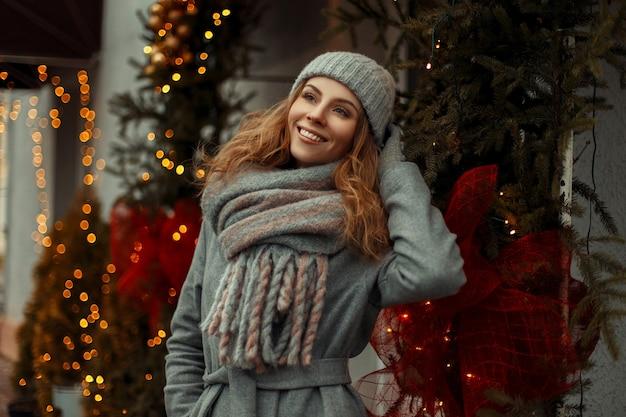 Bella ragazza di smiley felice in vestiti di moda maglieria vintage con un elegante cappello e sciarpa su una vacanza di natale Foto Premium