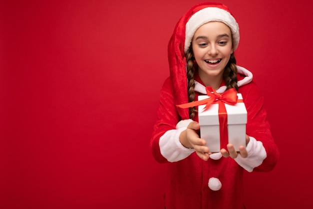 Bella ragazza castana sorridente felice isolata sopra la parete rossa che porta l'attrezzatura del babbo natale che tiene il contenitore di regalo bianco con il nastro rosso. spazio vuoto