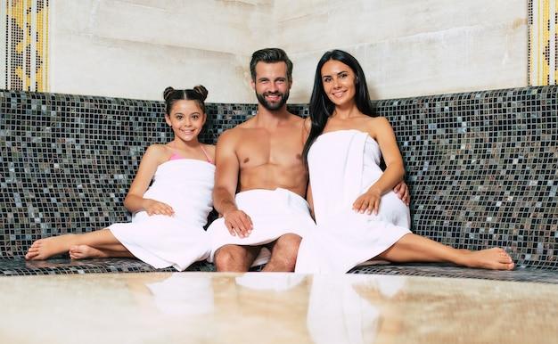 Bella famiglia sorridente felice in asciugamani da bagno sta guardando sulla fotocamera mentre ci si rilassa nella sauna o nell'hammam. procedura di vacanza e spa
