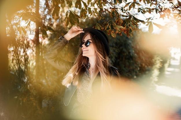 Bella ragazza sorridente felice con un viso carino in abiti alla moda con una giacca di pelle, abito elegante, occhiali da sole e un cappello viaggia nel parco in una giornata di sole autunnale